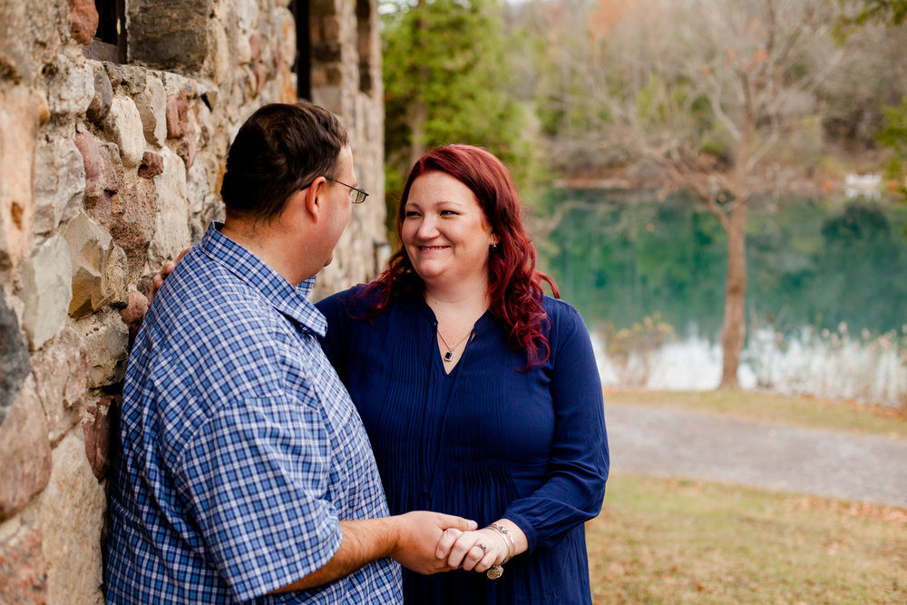 Man and woman smile at each other while leaning against a stone building. Image by Syracuse Wedding Photographer, Calypso Rae Photography.