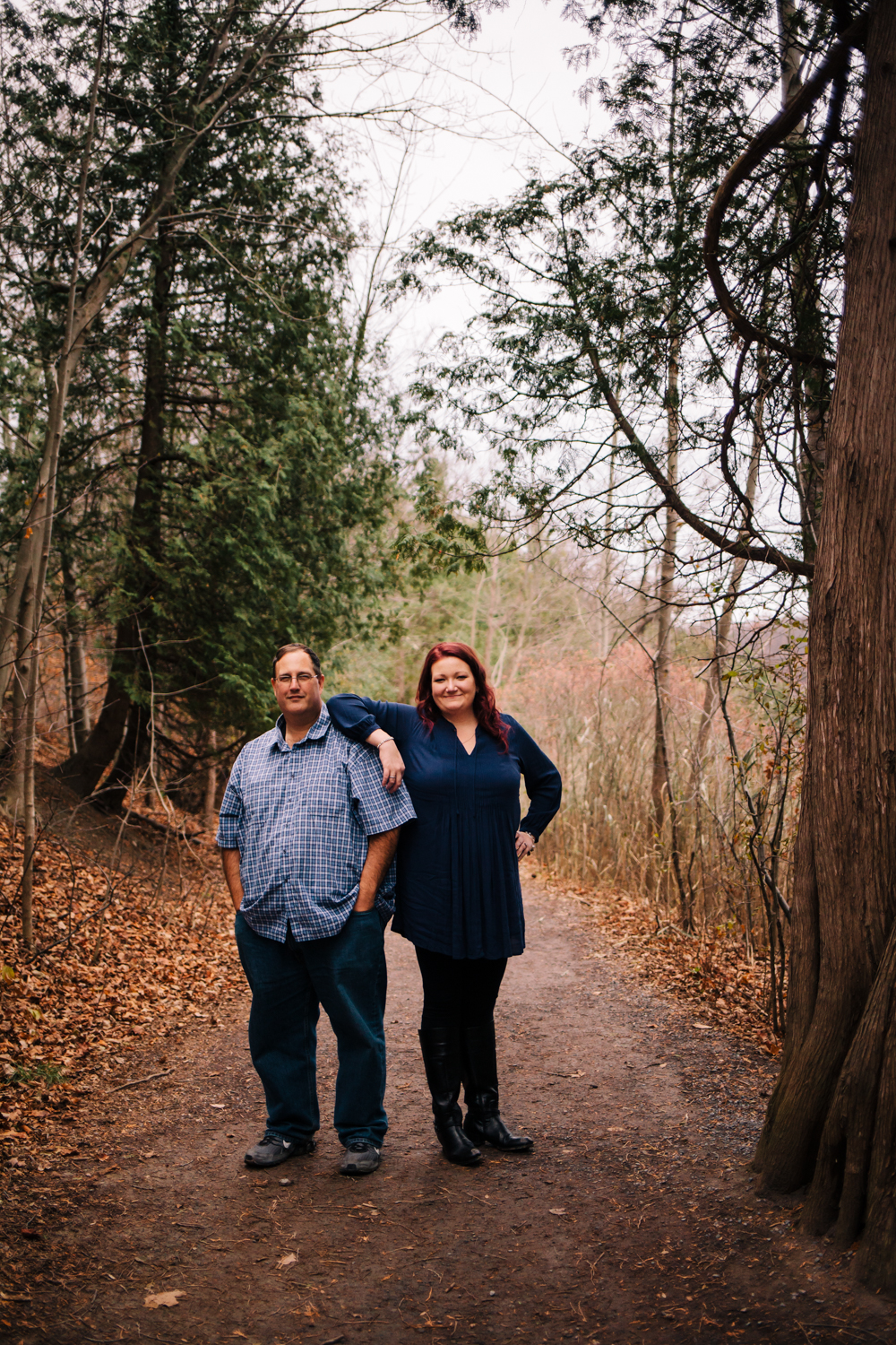Woman stands with arm on mans shoulder. They are in the woods on a trail and wearing navy blue shirts. Engagement photograph taken by Calypso Rae Photography.