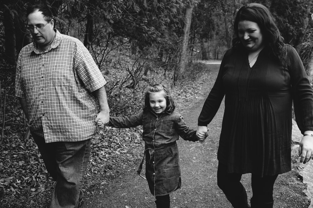 Black and white image of a family walking through the woods. A young girl is in between her mom and dad.