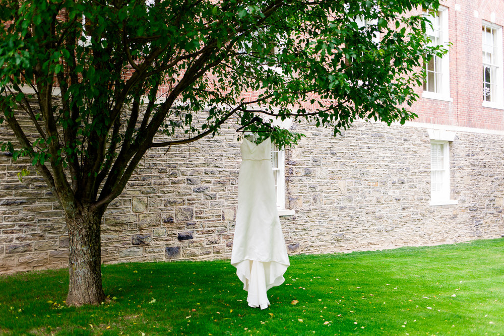 Elegant white dress hangs from tree at the Otesaga Resort in Cooperstown, NY.