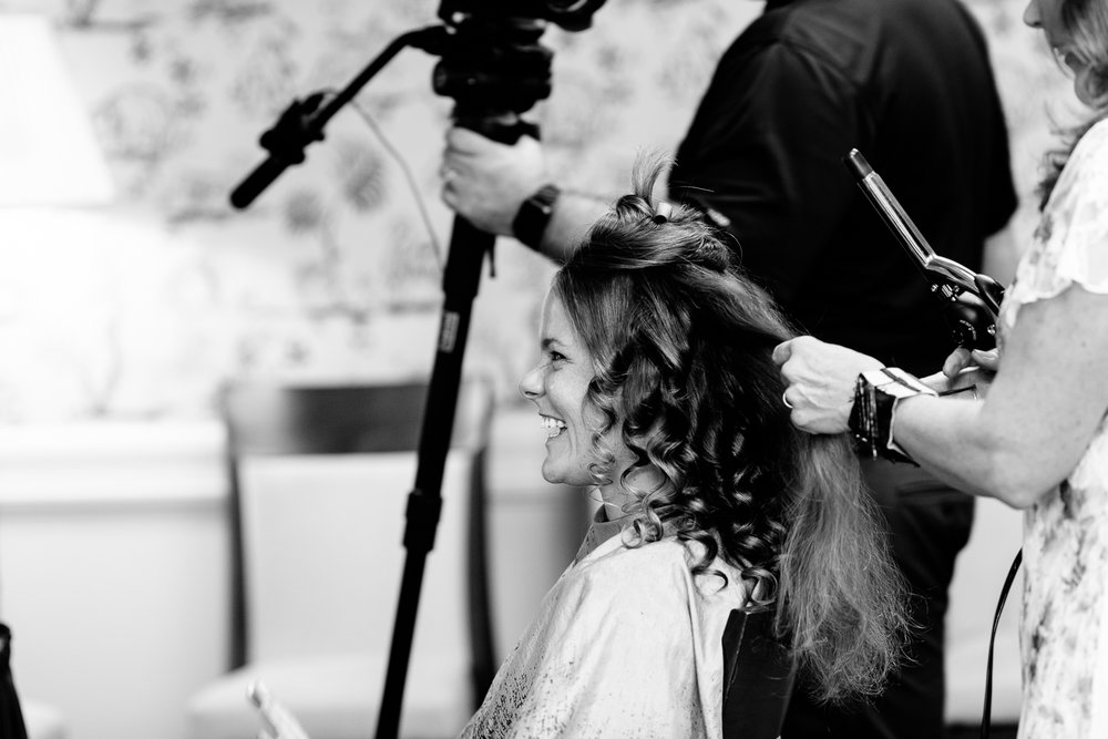 Bride laughs while getting her hair done.