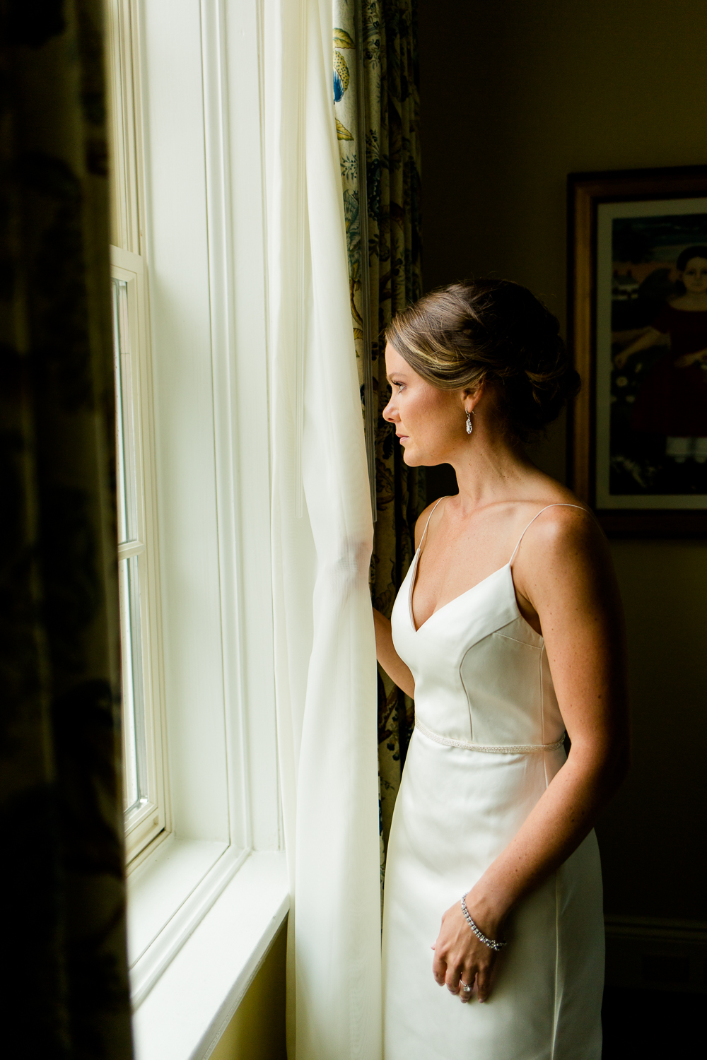 Bride looks out the window on her wedding day.