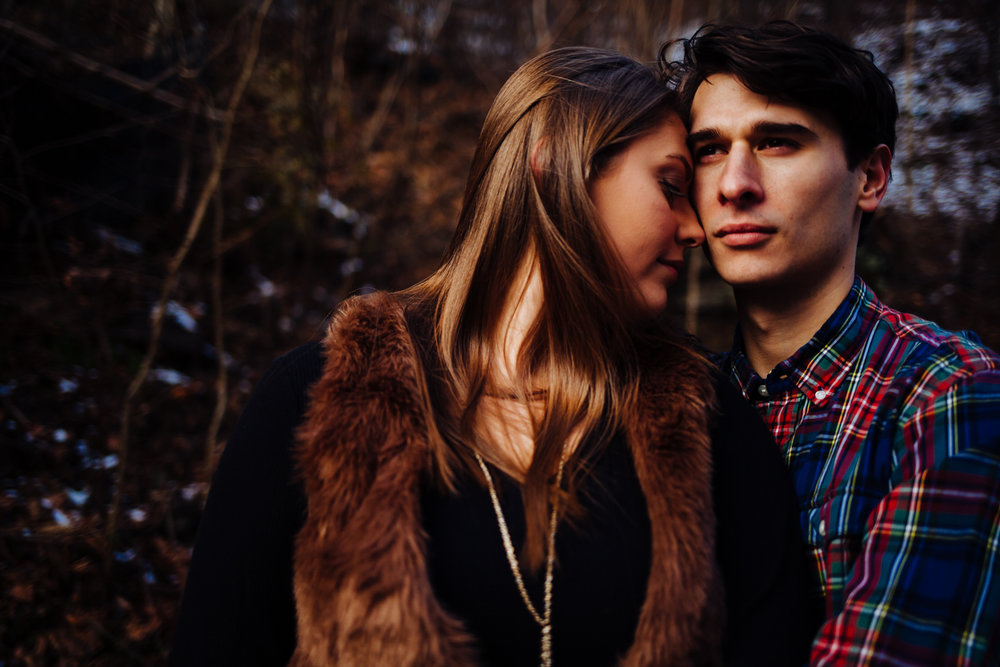 Close up of man and woman during a winter engagement shoot. She wears a fur vest and he has a plaid shirt on.