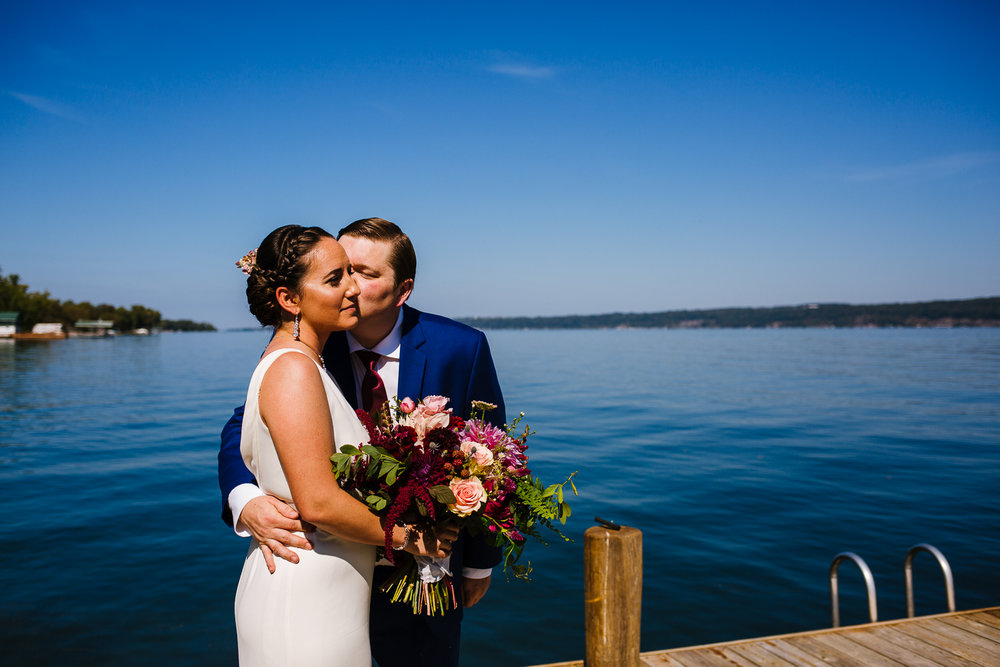 Groom kisses bride on cheek on a dock.