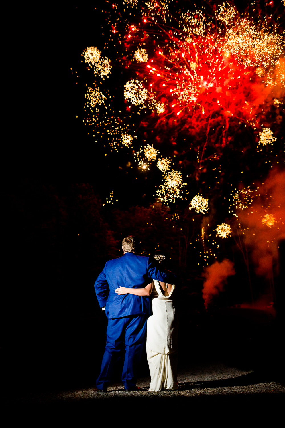 Bride and groom look out at fireworks at New Park Retreat in Ithaca, NY.