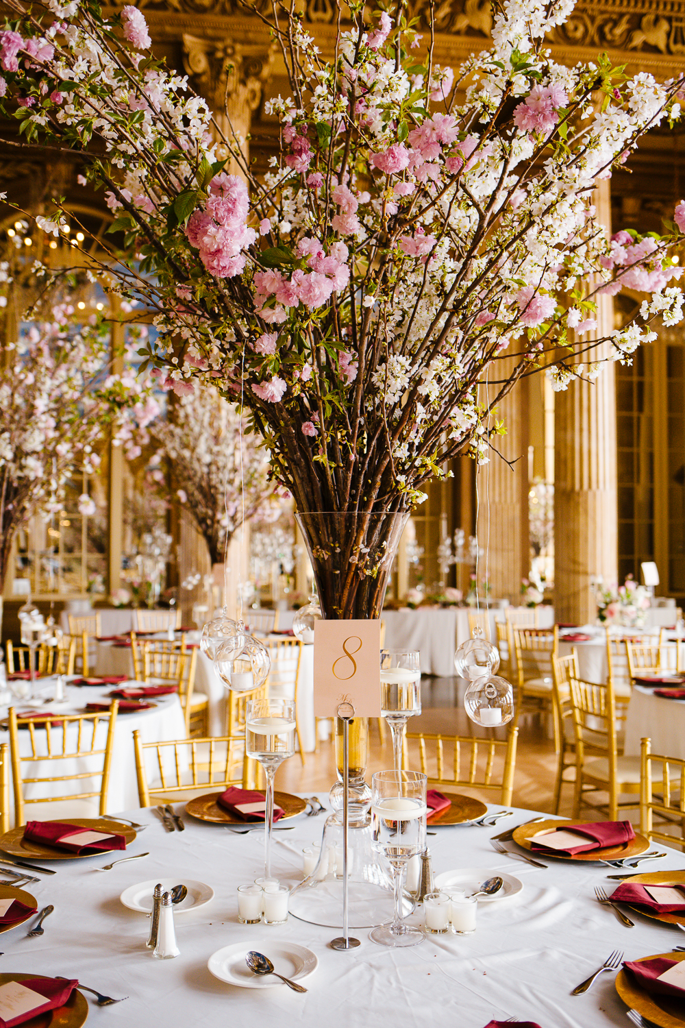 Tablescape at a wedding reception in Syracuse, NY. The table is labled as table 8 and has cherry blossoms as the centerpiece.