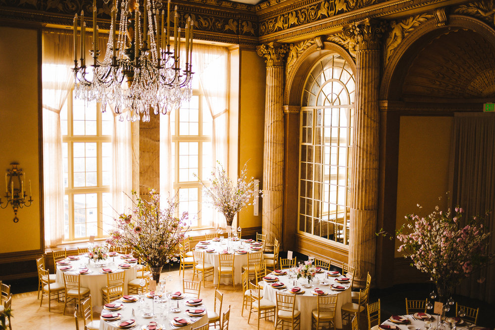 A wide shot of the grand ballroom at the Marriott Syracuse Downtown. The room is golden and ornate with large floor to ceiling windows and hanging crystal chandeliers. The tables are decorated with Cherry Blossoms. The image was produced by Calypso Rae Photography.