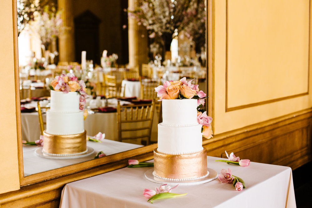 A white and gold wedding cake is adorned with pink and orange flowers. A mirror is behind the cake causing a reflection of the cake to be seen as well as the tables in the room.