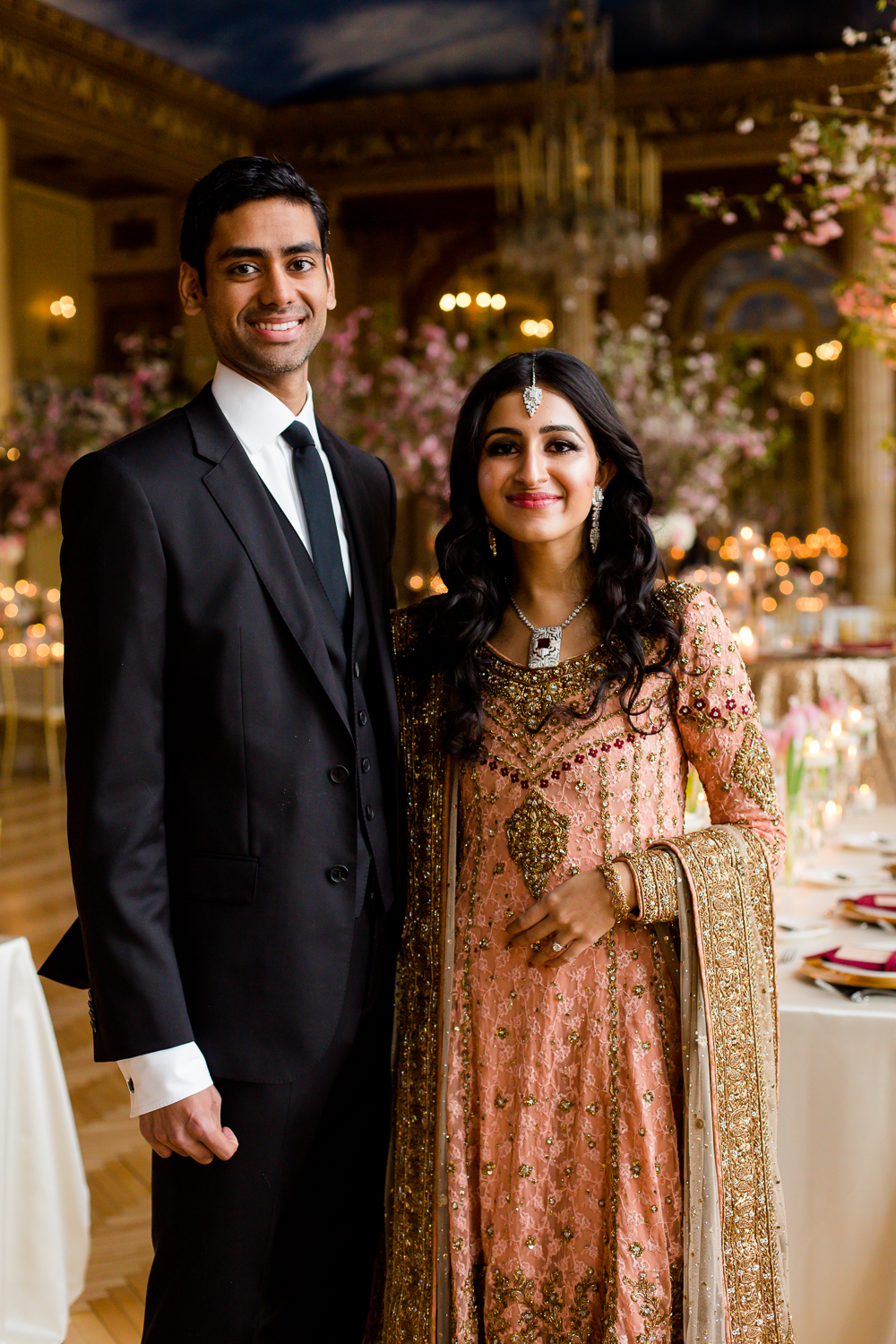 A bride and groom pose in the ballroom of their wedding reception. The bride is dressed in traditional Pakistani dress. The groom is in a suit.
