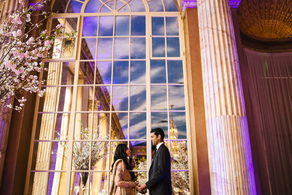 Portrait of a bride and groom in front of a huge mirror that goes to the ceiling of the ballroom.