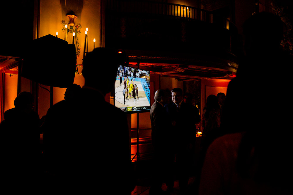 Silhouette of people watching march madness at a wedding reception
