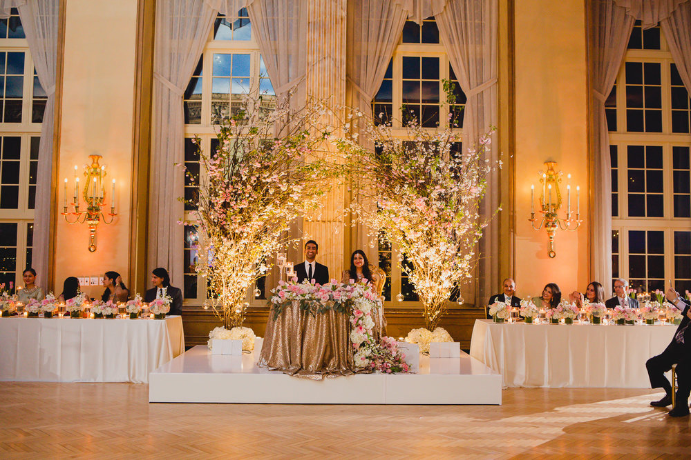 Bride and groom seated at their sweet heart table, surrounded by their parents and siblings.