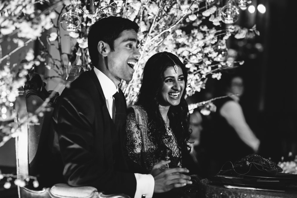 Black and white image of bride and groom laughing during their wedding reception.