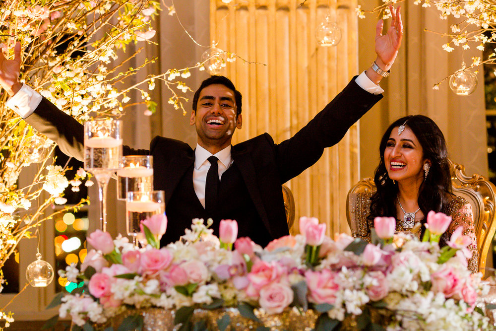 Bride laughs, while groom raises his hands in joy during their wedding reception.