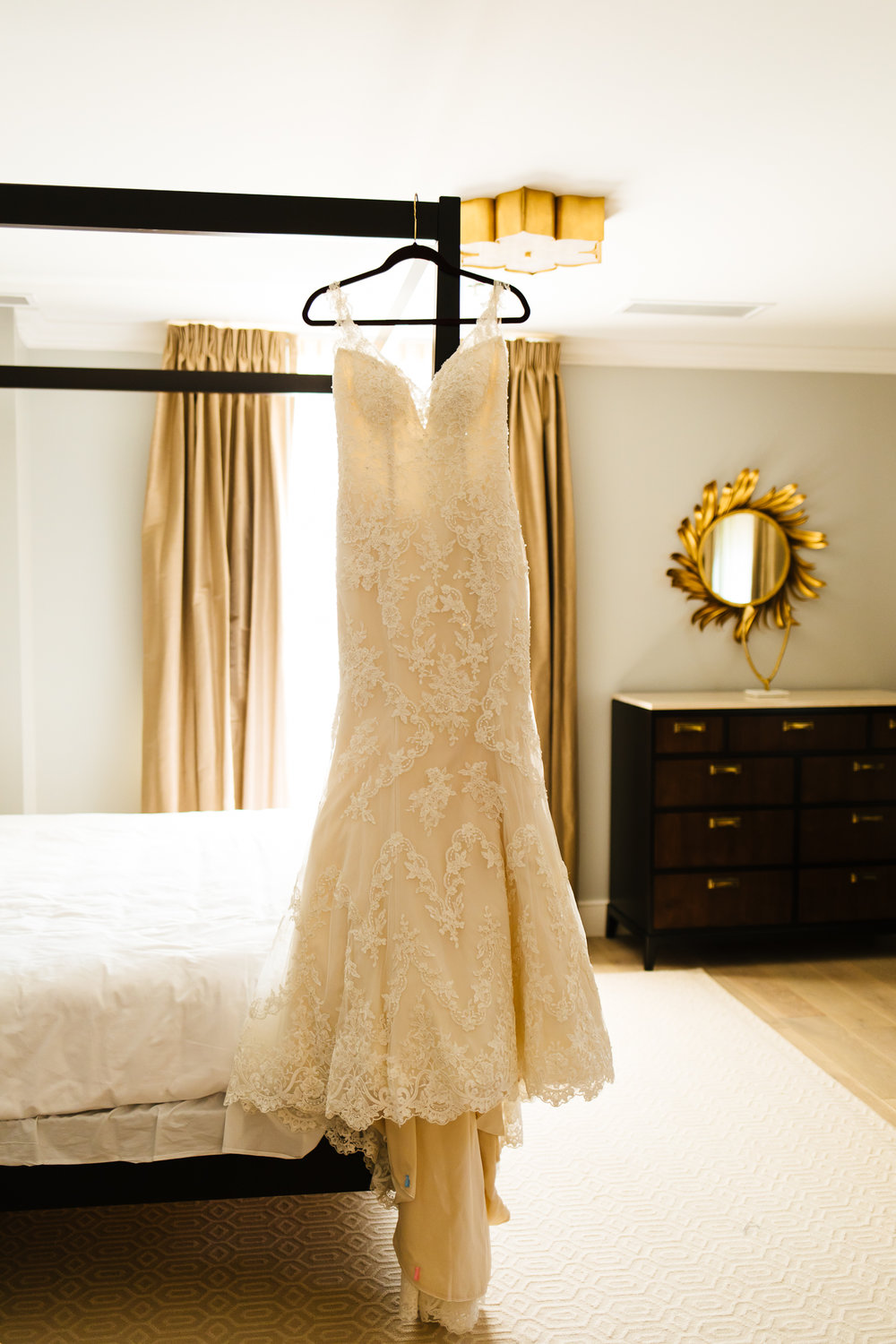 White Maggie Sottero wedding gown hanging from a bed. Image by Calypso Rae Photography