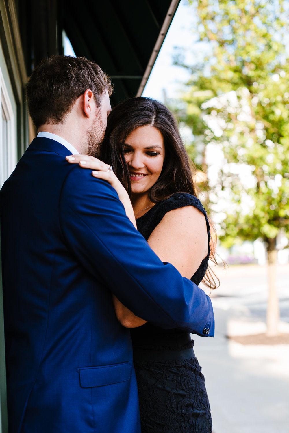 Woman in a black dress snuggles up to man in a blue suit.