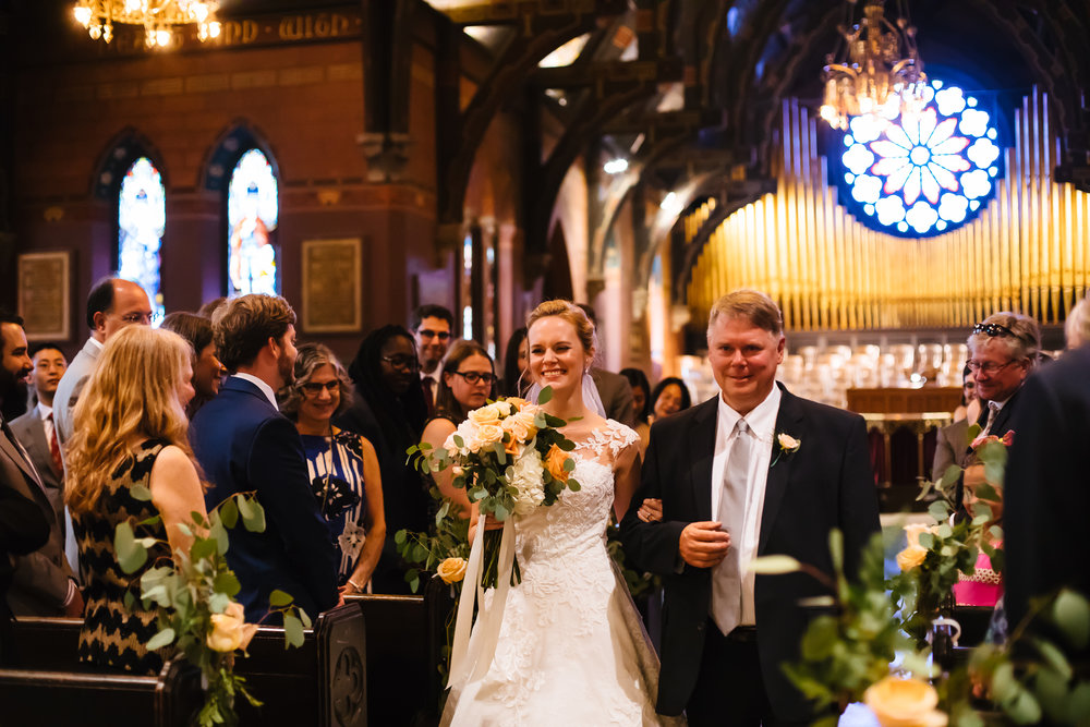 Bride walks down the aisle with her father in Sage Chapel in Ithaca, NY.