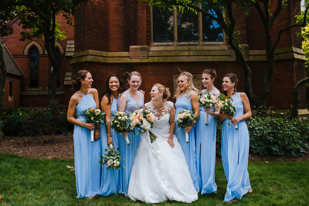 Bride and Bridesmaids laugh. The Bridesmaids have sky blue dresses on.
