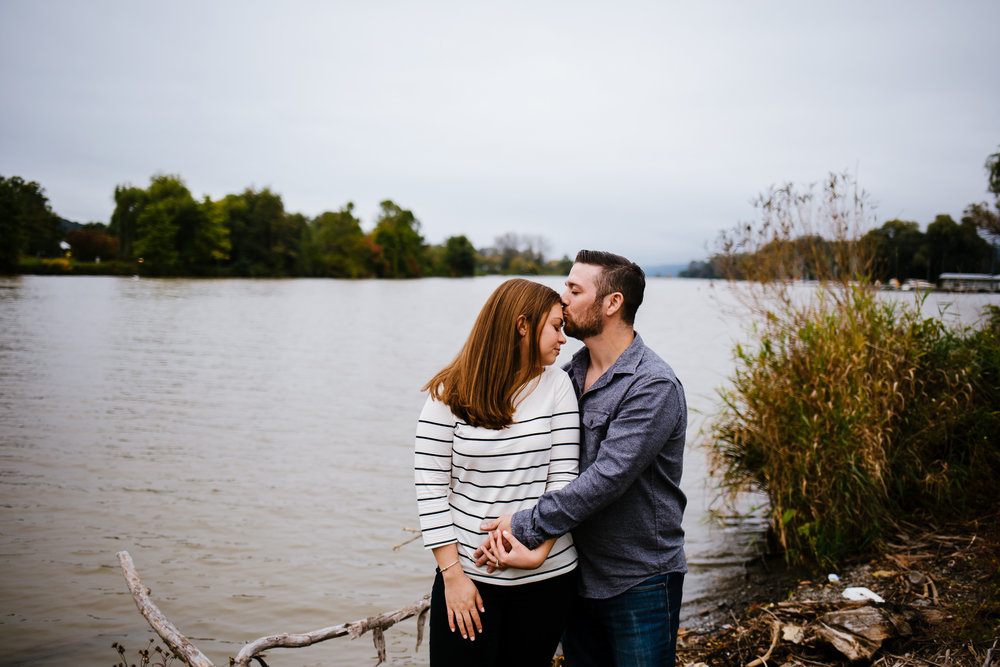 Man kisses his partners forhead. They are standing in front of a lake.