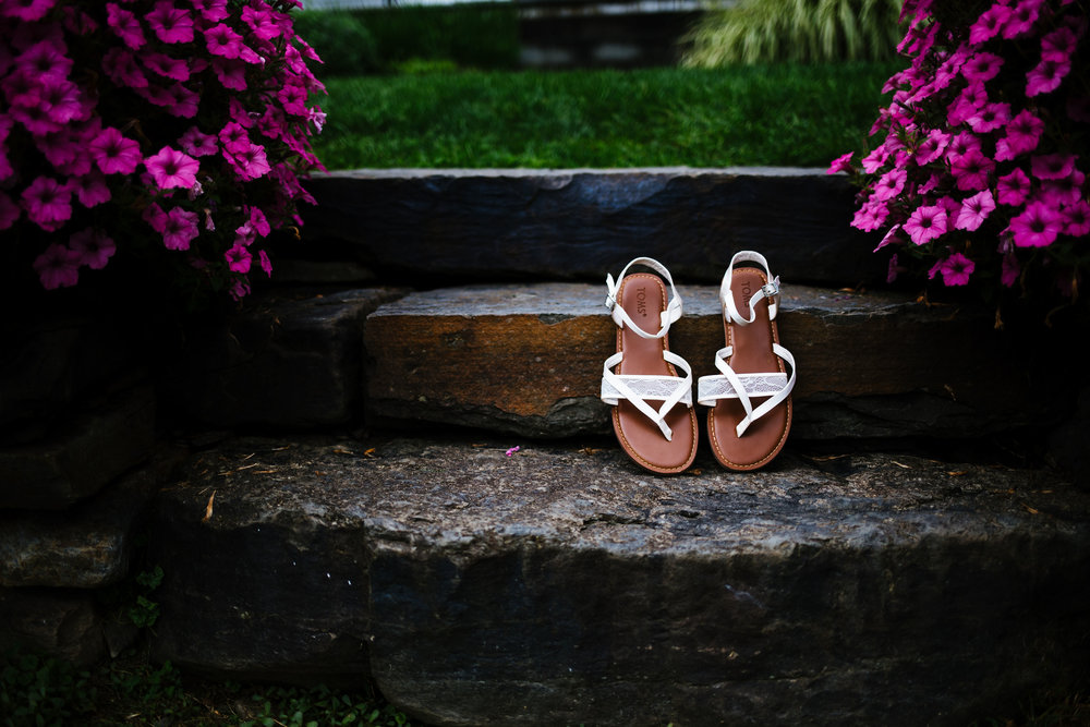A bride's wedding shoes rest on stone steps. They are white lace sandles. They are surrounded by vibrant pink flowers.