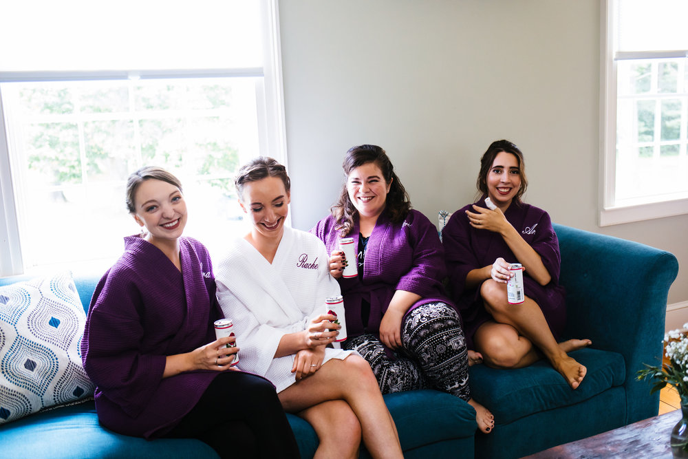 Bridesmaids and bride sit together on a blue couch. The bridesmaids have purple robes on and the bride has a white robe on.