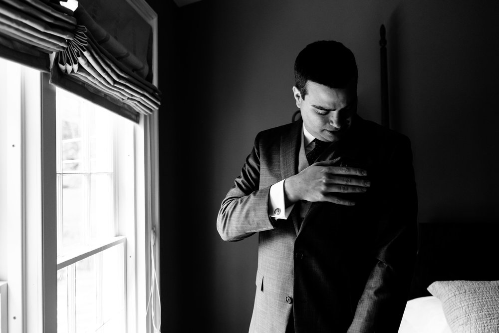Black and white image of a groom getting ready at the Fontainebleau Inn.