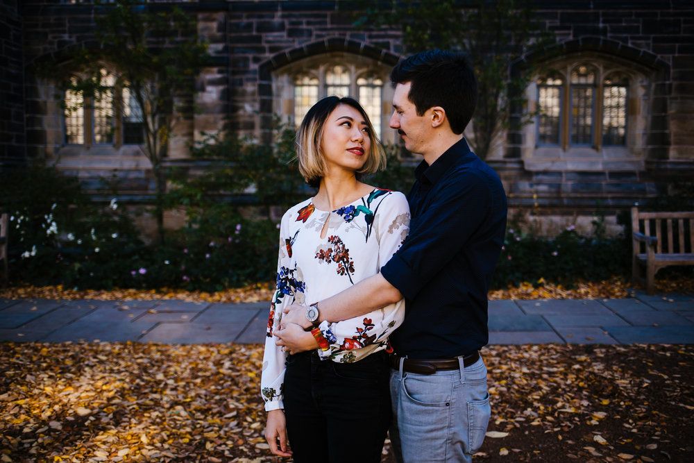 A woman gazes up at a man as they embrace on the quad of Yale University.