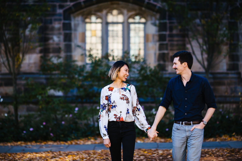A couple laughs while walking during their engagement shoot in New Haven, CT.
