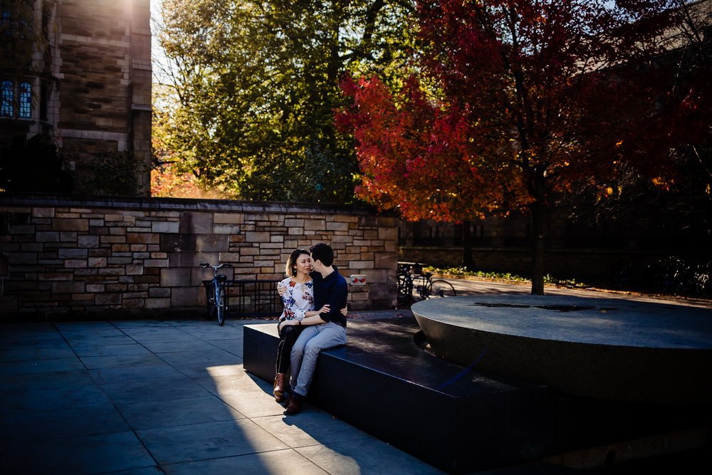 Couple sits near a fountain on the Yale Campus.