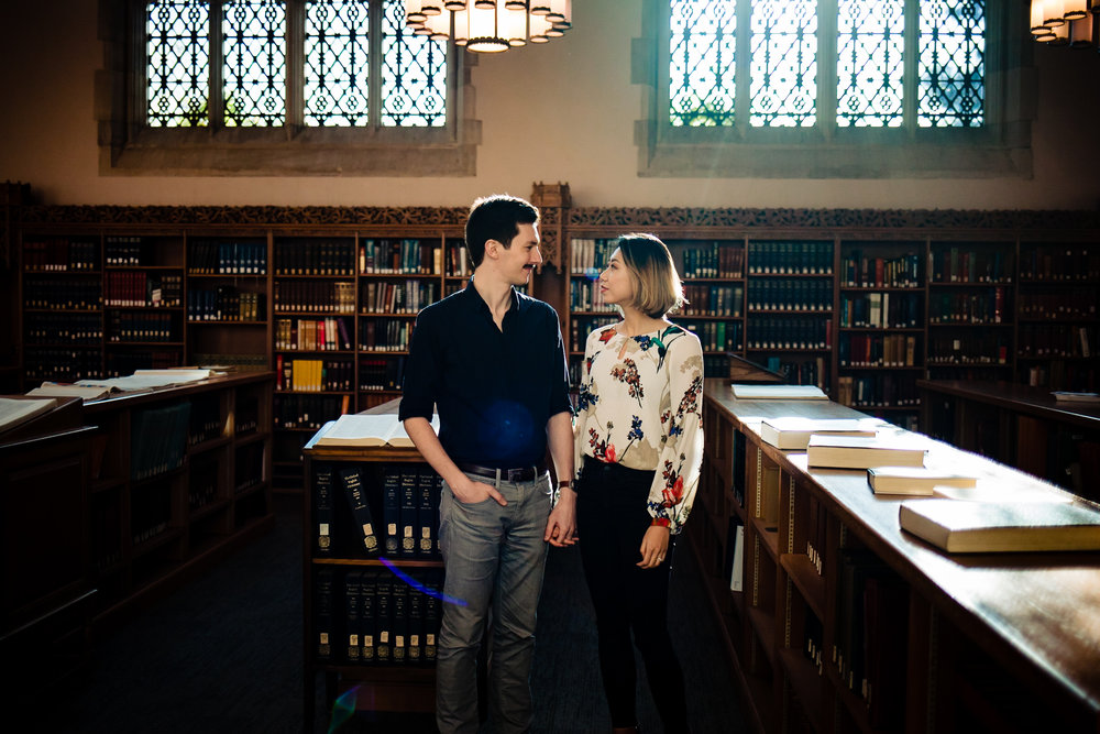 A couple stands in the library at Yale during their engagement session.