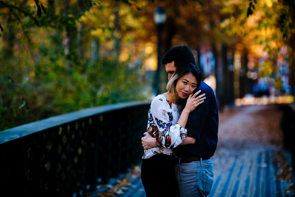 Man and woman hug on a bridge in the fall with vibrant foliage around them. In New Haven, CT.