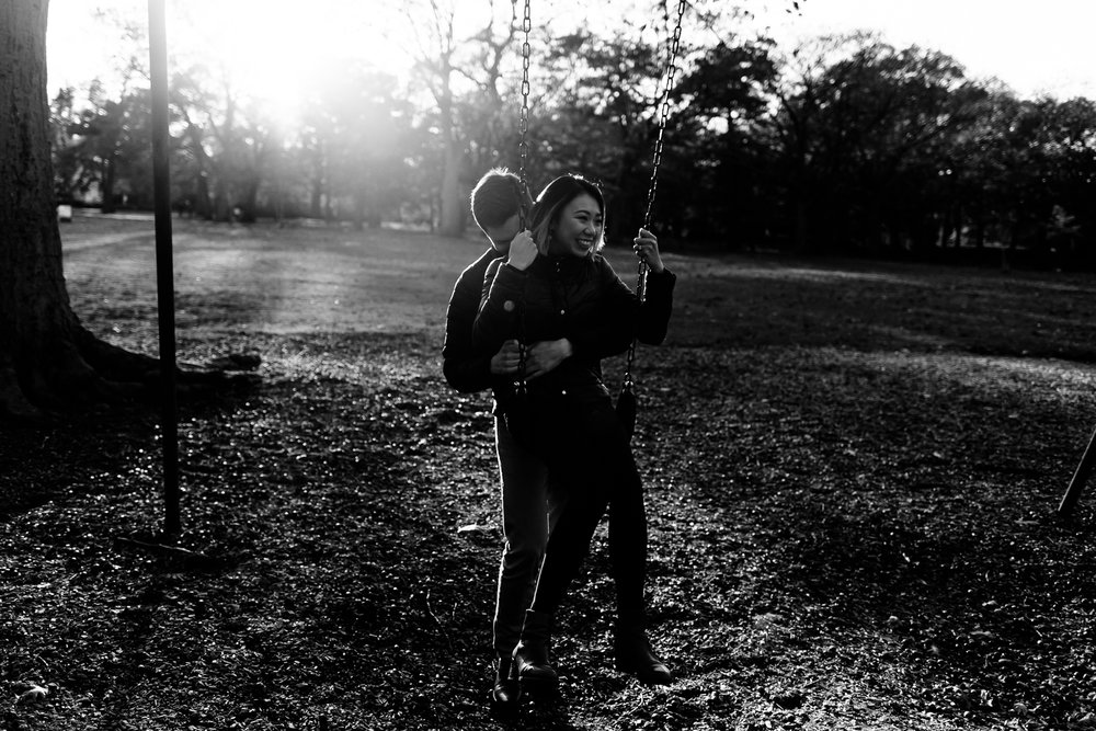 Black and white image of a couple laughing while using a playground swing