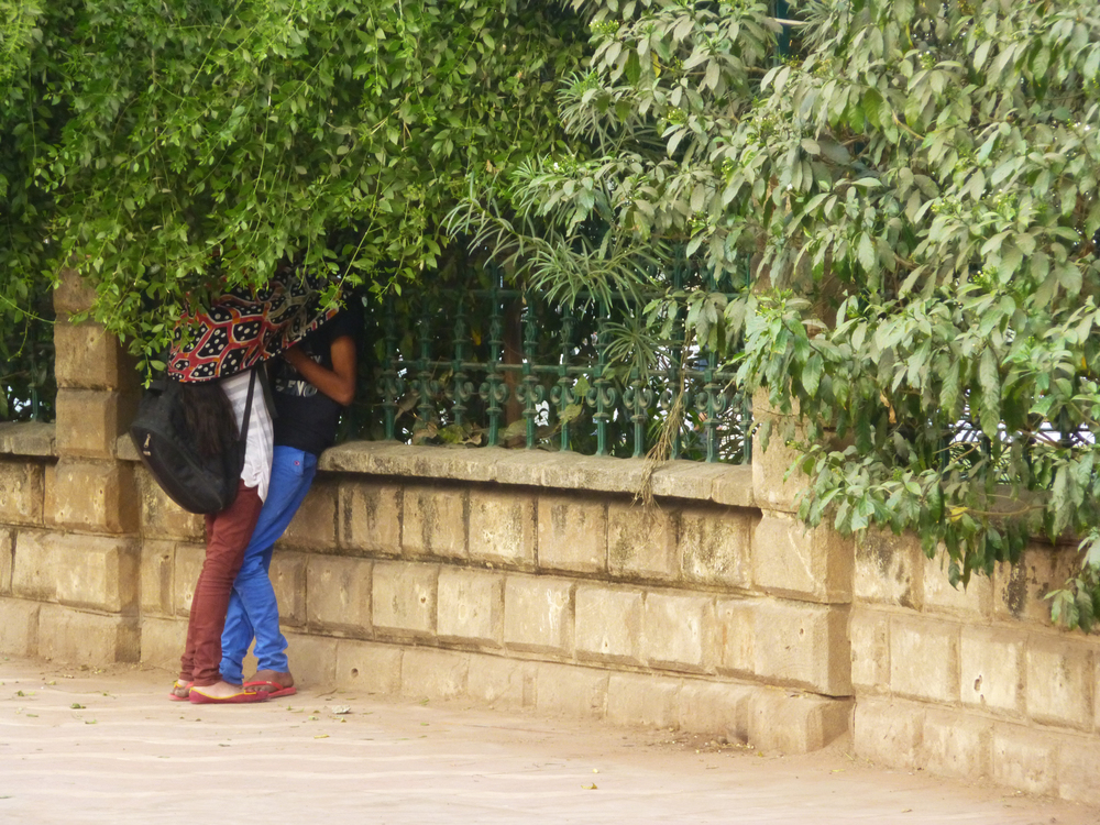 A young couple getting some time alone at the entrance to a park in the city