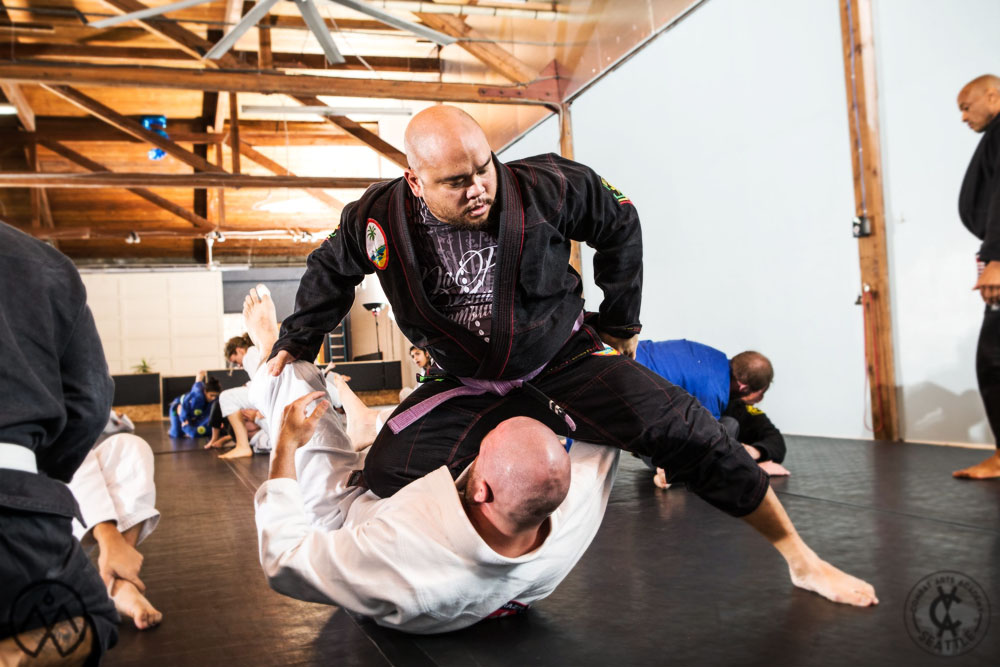A purple belt Belton Lubas practicing the Knee on Belly position during a BJJ seminar, crushing both the ribs and dreams of his training partner.