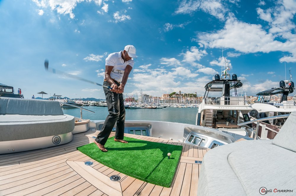 Francis Jacquemin, pro golf trainer practices his swings on board a super yacht.