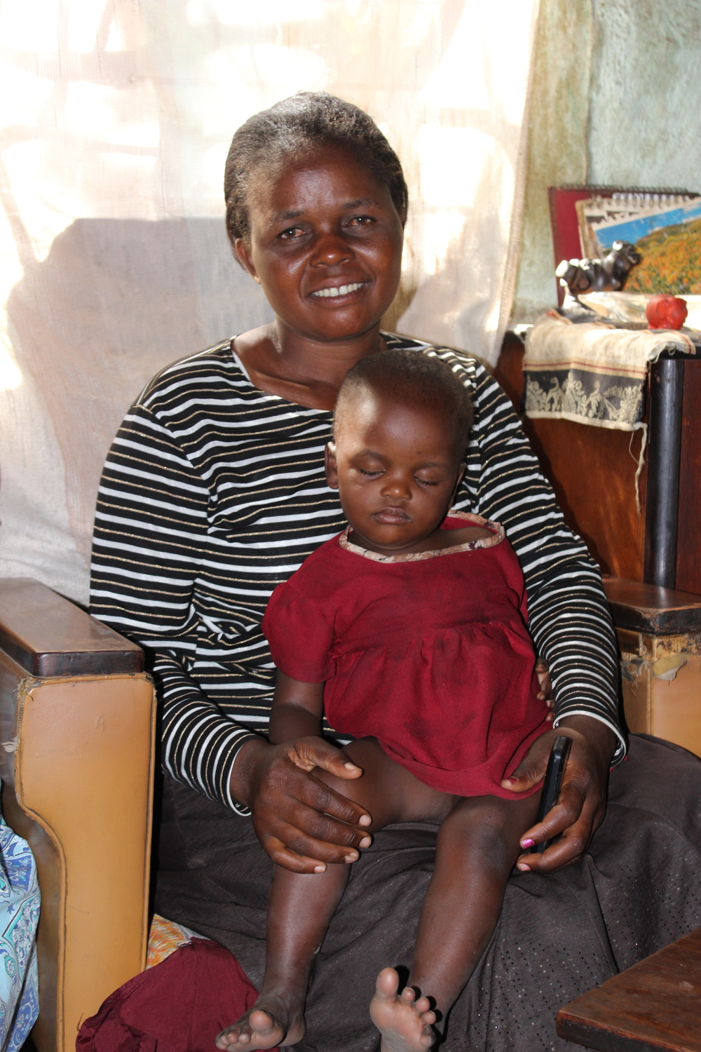 Florence, a care worker in Sukubva, holds Racheal, who falls asleep on her during our home visit.