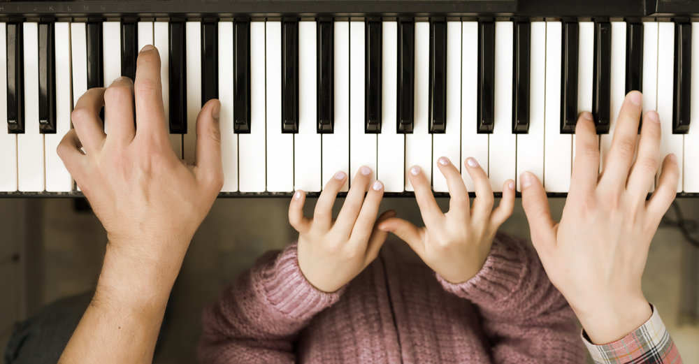 Piano Keyboard top View and Hands of Child Mother and Father