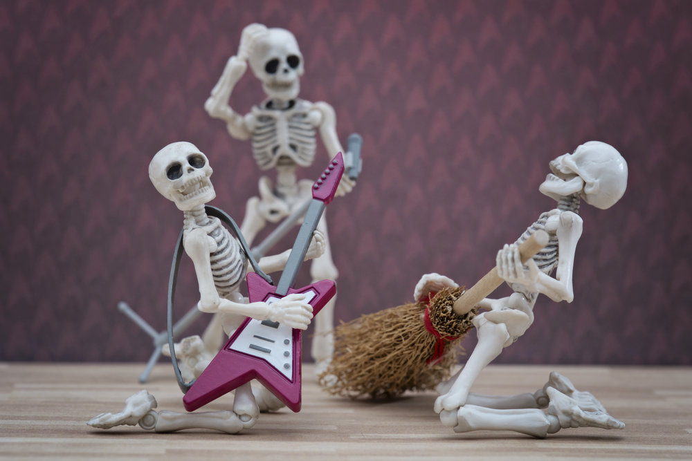 Skeleton playing broom as guitar