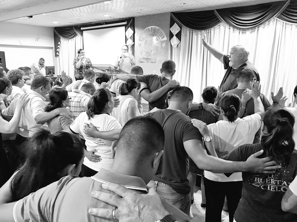 Johnny Moffitt praying over the Ministry Leaders at Puerta del Cielo in La Ceiba, Honduras.