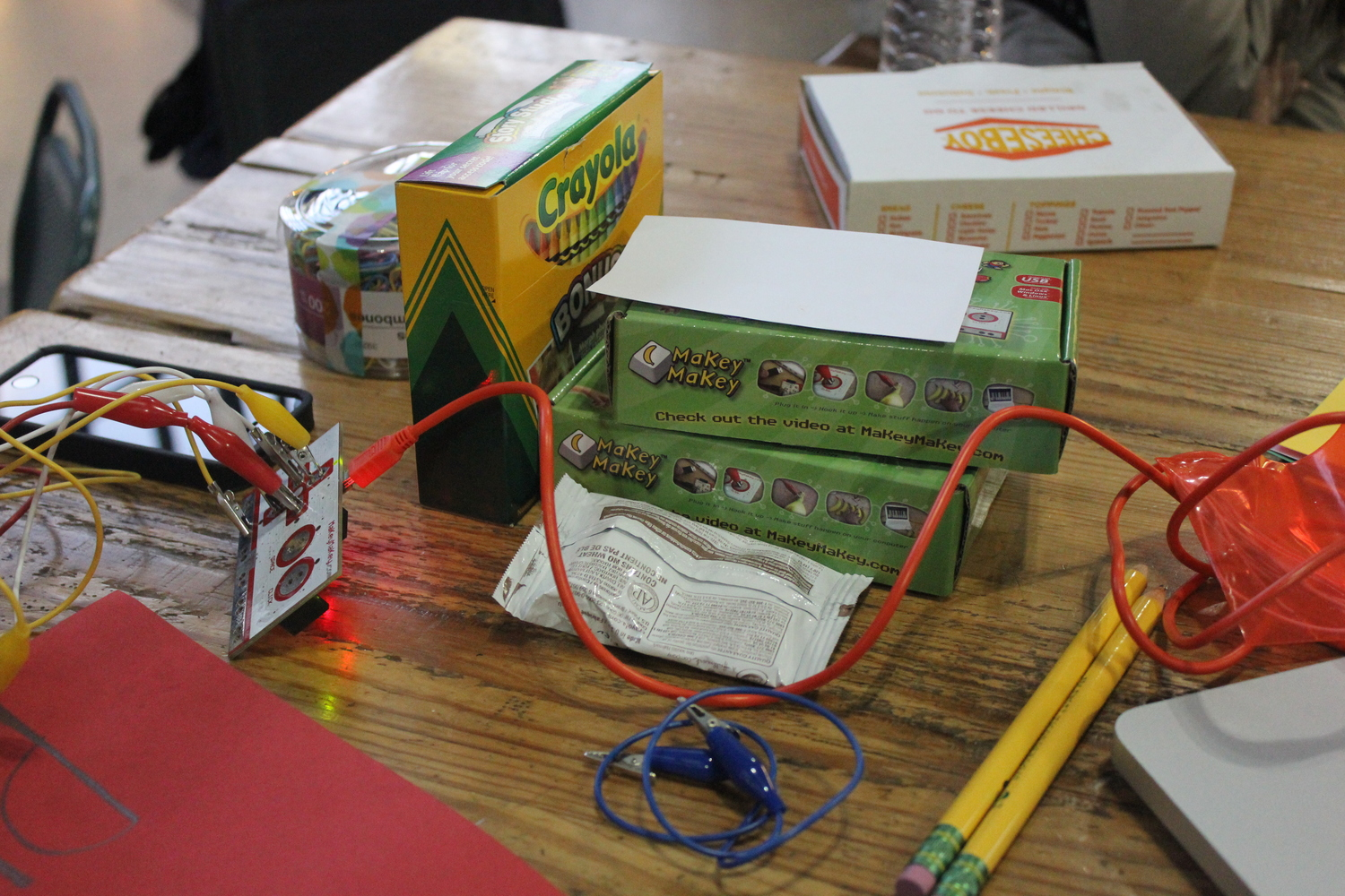 Wires, crayons, pencils, and two boxes of the makey-makey kit on a wooden table
