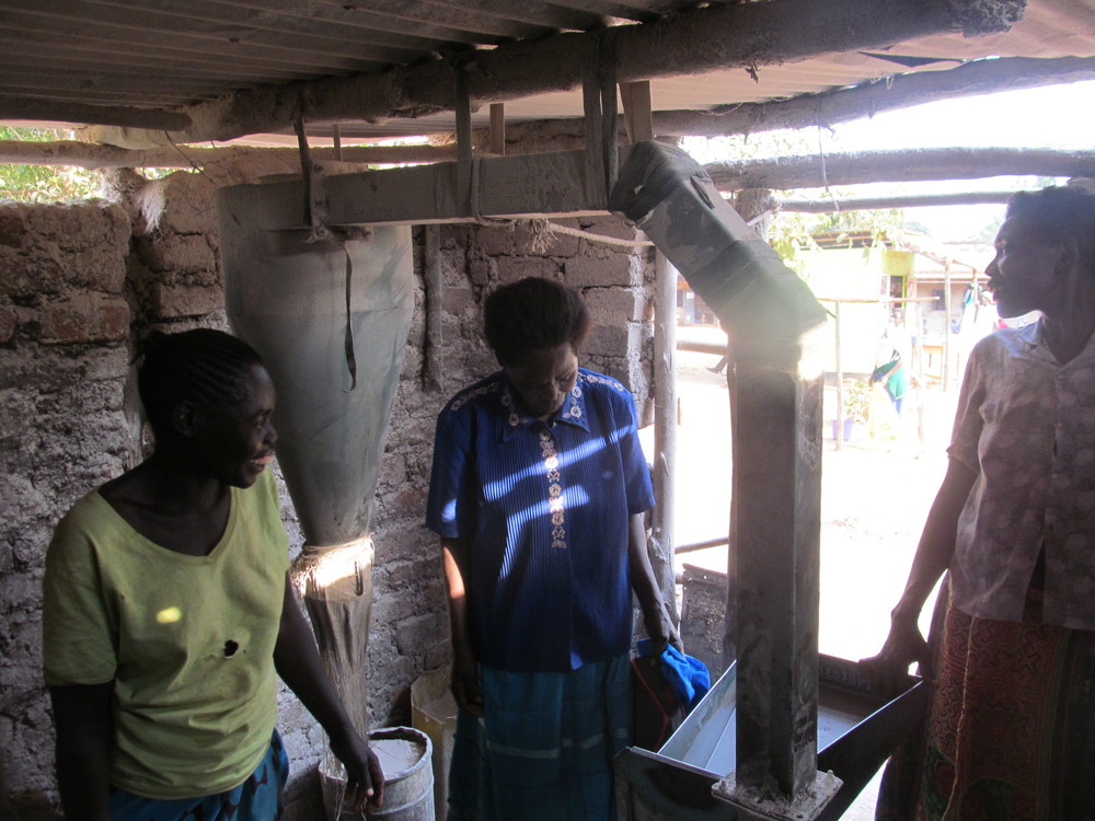Three group members working the corn grinding mill, they are so happy for this opportunity!
