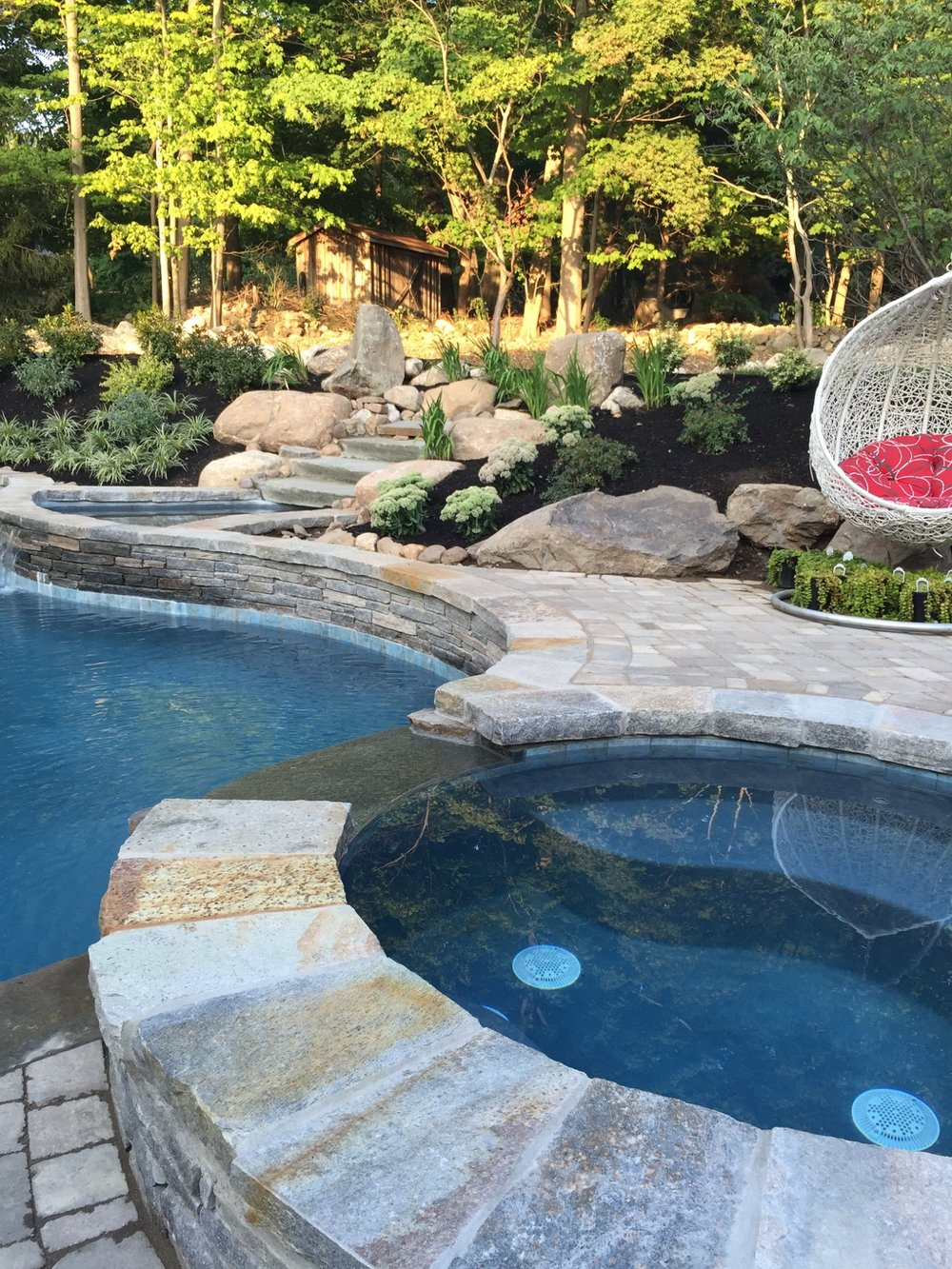 New Jersey custom lagoon with bar stools, spill over spa and natural rock waterfall.