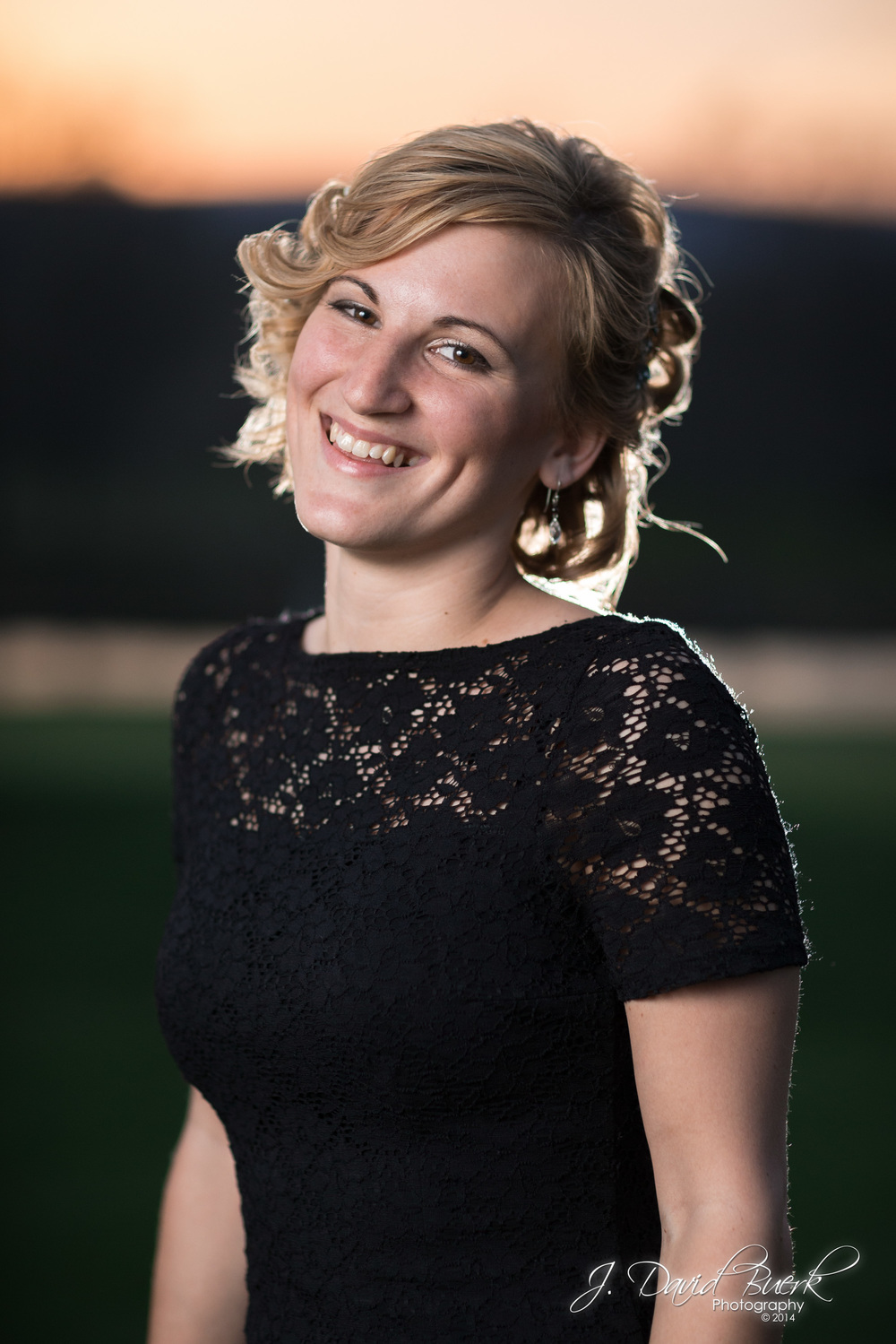 A maid of honor smiles for a test shot as I set up my lighting at sunset during a wedding.