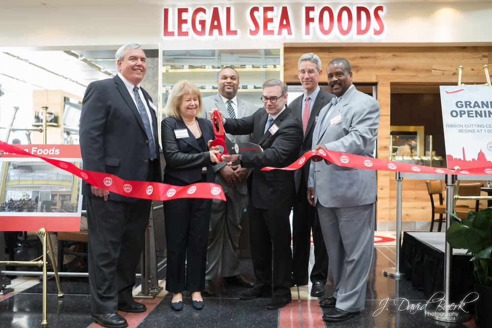 Restaurant owners and management cut the ribbon at a newly opened Legal Sea Foods at Ronald Reagan National Airport.