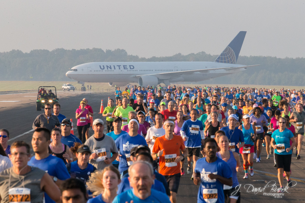 5K and 10K runners pass a United Airlines 757 on R/W 1R during the 2014 Dulles Day Plane Pull.