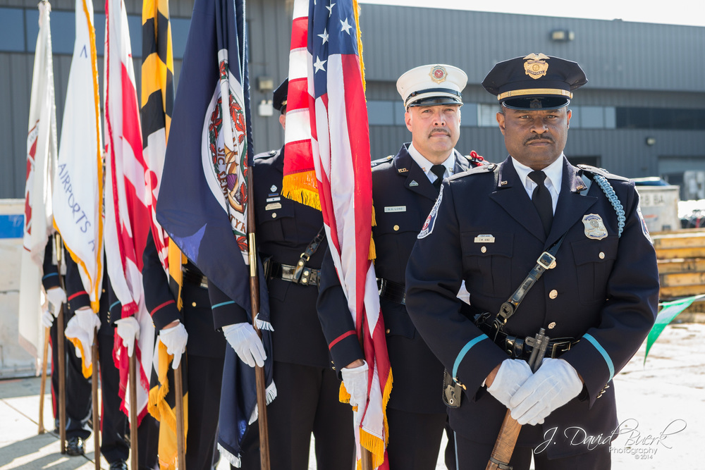 Fire and Police Officer Color Guard stand at the ready during the Opening Ceremony of 2014's Dulles Day Plane Pull and 5K / 10K on the Runway.