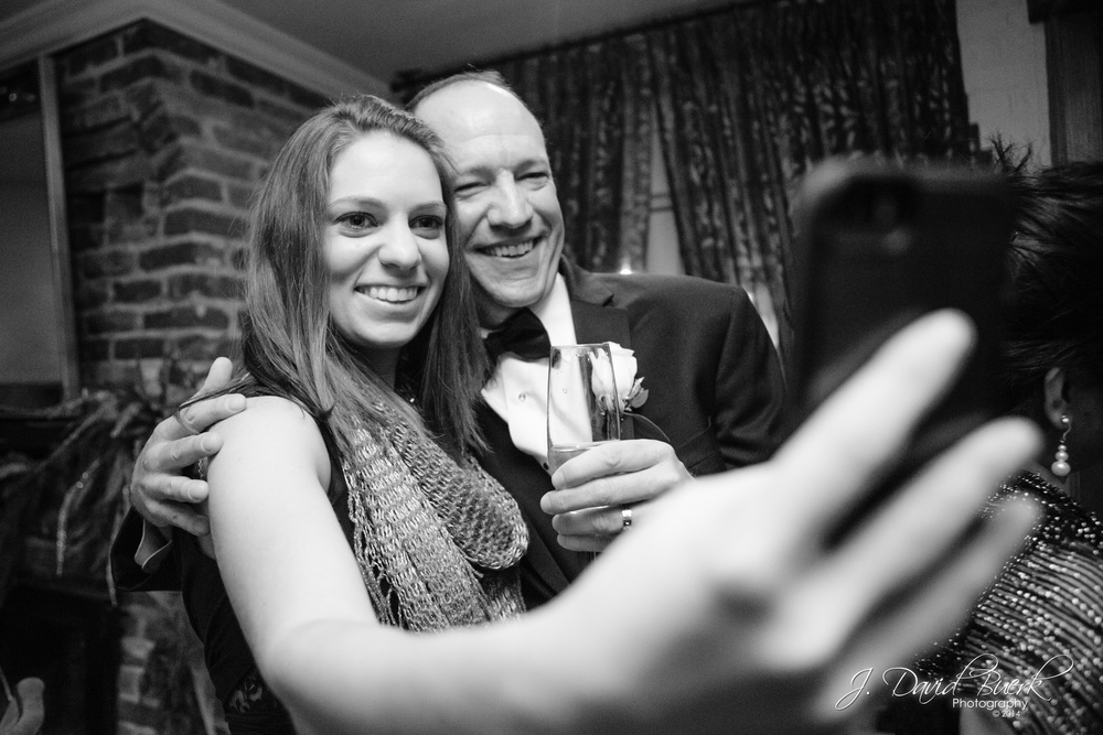 "A groom takes a selfie with a wedding guest.  ""Selfie"" was 2014's Word of the Year."