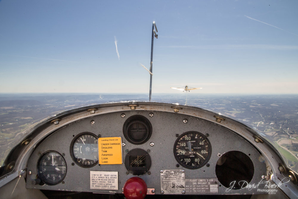 View inside the cockpit of a glider being towed to 2,500ft before release of the tow cable.  The tow plane is visible directly forward, with instrumentation on the console and the red lever which releases the tow cable.