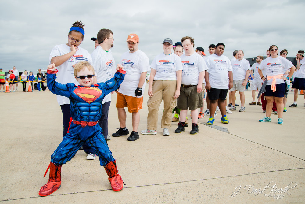 """Superman"" leads the way at the 23rd annual Dulles Day Plane Pull benefitting Special Olympics.  The Special Olympics team is always the first team to pull the FedEx 757 to kick off this family fun charity event which draws 10,000 - 15,000 visitors every year."
