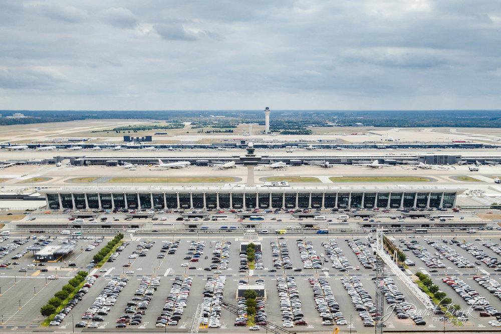 "Aerial photograph of Washington Dulles International Airport's iconic Main Terminal Building designed by architect Eero Saarinen.  Cranes which are part of the ""Silver Line"" rail construction project can be seen at the bottom of the frame, as construction of the Dulles Metro Station commences.  Photographed via helicopter, 500ft AGL."